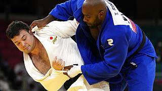 Aaron Wolf of Japan, left, and Teddy Riner of France compete during their gold medal match in team judo competition at the 2020 Summer Olympics, Saturday, July 31, 2021,.