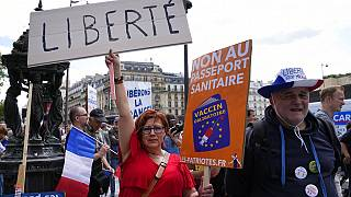 """A protestor holds a sign which reads in French, """"freedom"""" and """"no to the Covid passport"""" as she attends a demonstration in Paris, France, Saturday, July 31, 2021."""