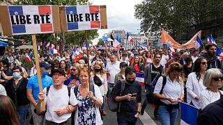 """متظاهرون يرفعون لافتات كُتب عليها بالفرنسية """"الحرية"""" بينما يلوح آخرون بالأعلام الفرنسية أثناء مشاركتهم في مظاهرة في باريس، فرنسا، السبت 31 يوليو 2021"""