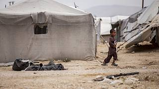 A boy holds a book as he walk at al-Hol camp, which houses families of members of the Islamic State group, in Hasakeh province, Syria, Saturday, May 1, 2021.