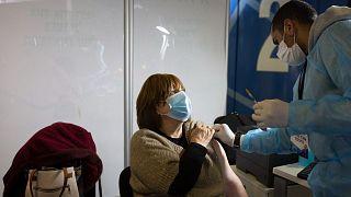 أخصائي طبي يستعد لإعطاء لقاح فايزر لامرأة في مركز تطعيم مؤقت في القدس، الخميس 14 يناير 2021