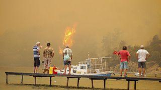 A strandtól méterekre tomboló tüzet nézik egy stégről turisták a törökországi Bodrumnál