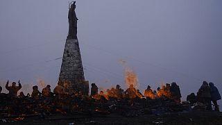 Decenas de personas realizan ofrendas a la Pachamama en La Cumbre, cerca de La Paz, junto a una estatua de Jesucristo.