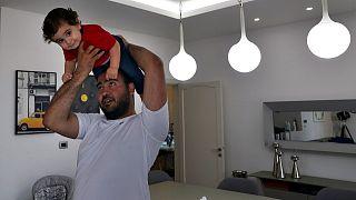 إدموند خنيصر مع طفله جورج في بيتهما في جل الديب شمال بيروت، 10 يوليو 2021
