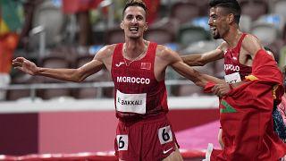 المغربي سفيان البقالي يحتفل مع مواطنه محمد تندوفت بفوزه بذهبية نهائي سباق 3000 متر حواجز في دورة الألعاب الأولمبية الصيفية 2020 في طوكيو.