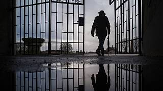 In this Sunday, Jan. 27, 2019 file photo a man walks through the gate of the Sachsenhausen Nazi death camp with the phrase 'Arbeit macht frei' (work sets you free)