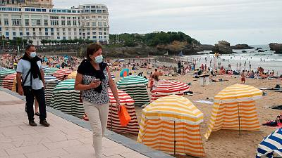 People wearing face masks to protect against COVID-19 walk past a beach in Biarritz, southwestern France, July 28, 2021.