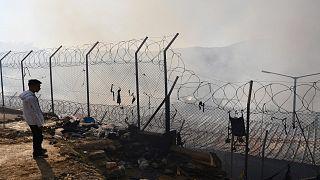 ARCHIVO - El 11 de noviembre de 2020 un migrante se encuentra fuera de un campamento de refugiados después de un incendio en la isla