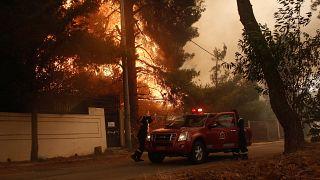Tűzoltók érkeznek az Athén Sztamata nevű külvárosában pusztító erdőtűz helyszínére 2021. július 27-én.
