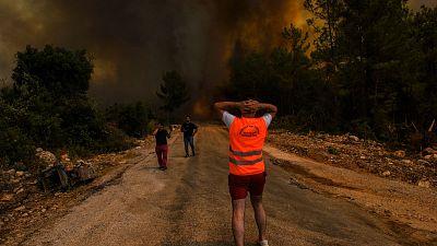People watch the fire raging over Antalya, Turkey, Sunday August 1