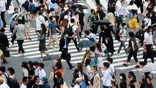 Japonya'nın başkenti Tokyo'da kalabalık bir caddede yürüyen vatandaşlar