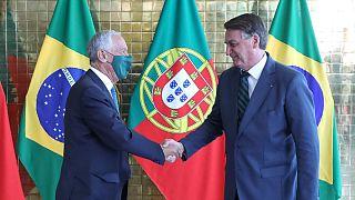 Mareclo Rebelo de Sousa, de máscara, aperta a mão a Jair Bolsonaro, sem máscara