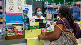 A pharmacist welcomes a client in Pointe-a-Pitre, on the French Caribbean archipelago of Guadeloupe, on July 30, 2021.