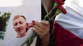 A young woman holds a picture of Belarusian activist Vitali Shishov outside the Belarusian embassy in Kyiv,  August 3, 2021