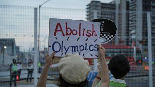 متظاهرون مناهضون للأولمبياد يحملون لافتات أمام السياج حول القرية الرياضية للألعاب الأولمبية الصيفية في طوكيو، اليابان، الجمعة 30 يوليو 2021