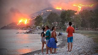 People on a beach watch the blazes spreading up a hill in the Aegean coast city of Oren, near Milas, in the holiday region of Mugla.