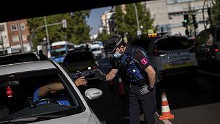 Un agente di polizia locale ferma un veicolo a un posto di blocco a Madrid, Spagna