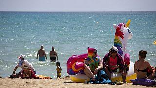 Turistas se bañan y toman el sol en una playa de Mallorca
