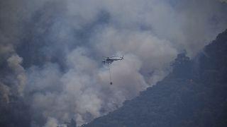 طائرة هليكوبتر لمكافحة الحرائق تلقي مواداً لإخماد النيران المشتعلة في الغابات بالقرب من منتجع مارماريس السياحي