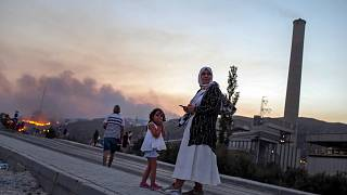 People stand in front of Kemerkoy Thermal Power Plant, right, as a wildfire approaches in the background, in Milas, Mugla, Turkey, Aug. 3, 2021.