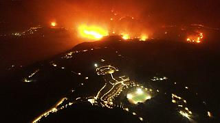 A wildfire approaches the Olympic Academy, foreground, in ancient Olympia, Wednesday, Aug. 4, 2021.