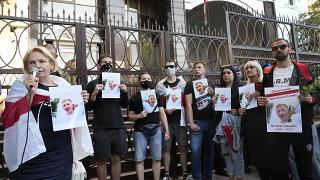 Activists hold portraits of activist Vitaly Shishov, leader of the Belarusian House in Ukraine, during a rally in front of the Belarus Embassy in Kyiv, August 3, 2021.