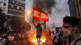 A protester stands with a Lebanese national flag during clashes with army and security forces near the Lebanese parliament headquarters in Beirut on August 4, 2021.