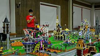 A person stands in front of a Lego metropolis including buildings, shopping complexes, cafes and parks.