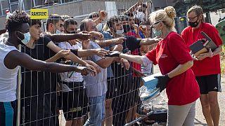 Litvánok árucikkeket adnak a menekülőknek a kordonon keresztül a verebiejai tábornál (illusztráció)