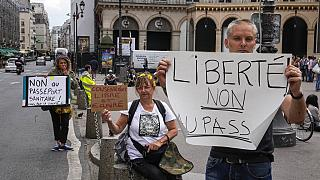 Anti heath pass demonstrators hold placards that read, liberty no to the health pass, outside the Constitutional Council in Paris, Thursday, Aug. 5,2021