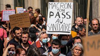 """Un manifestante antivacunas sostiene una pancarta en la que se lee """"Macron tu salud entra por el inodoro"""" durante una manifestación en París, el 17 de julio de 2021."""