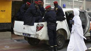 عناصر من الشرطة السنغالية يجلسون في سيارتهم بأحد الشوارع وسط العاصمة داكار