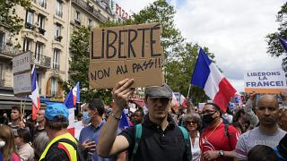 """متظاهر يحمل لافتة كتب عليها """"الحرية، لا للتصريح الصحي """" خلال مظاهرة في باريس، فرنسا."""