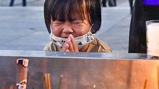 Una bambina prega di fronte al cenotafio di Hiroshima