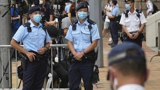 Police officers outside a court July 30, 2021, in Hong Kong, as pro-democracy demonstrator Tong Ying-kit exits after his sentencing for the violation of a security law.