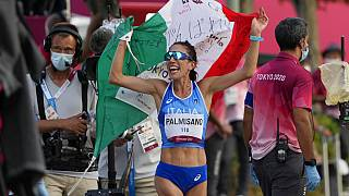 Antonella Palmisano of Italy holds the Italian flag after crossing the finish line of the women's 20km race walk.