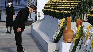 Japan's Prime Minister Yoshihide Suga pays his respects during a ceremony to mark the 76th anniversary of the Hiroshima atomic bomb attack.