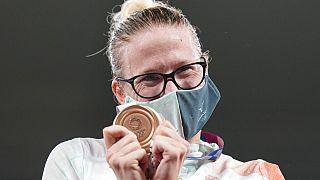 Sarolta Kovacs of Hungary celebrates on the podium with the bronze medal she won in women's modern pentathlon