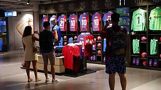 People take photos of Lionel Messi shirts on sale at the club's store before FC Barcelona club President Joan Laporta gives a news conference in Barcelona