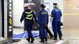 Tokyo Fire Department personnel and a police investigator, right, move toward a platform at Soshigaya Okura Station after stabbing on a commuter train
