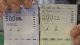 A man shows a one million bolivar note next to a twenty dollar note at a butcher's shop in western Caracas