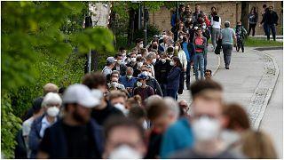 أشخاصٌ يصطّفون في طابور أمام مركز طبي في منطقة إبيرسبيرج القريبة من مدينة ميونيخ بألمانيا لتلقي جرعة من اللقاح المضاد لفيروس كورونا