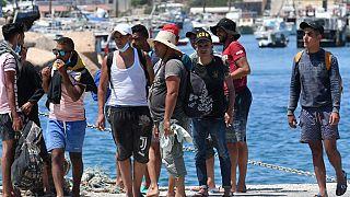 Migrants from Tunisia disembark from a 'Guardia di Finanza' patrol boat, on the Italian Pelagie Island of Lampedusa on August 1, 2020.