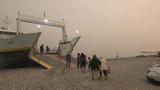 سكان جزر إيفيا اليونانية  يلجؤون إلى سفينة بعد الفرار من الحرائق.