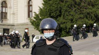 Rendőrök védik a szigorítás-ellenes tüntetőktől a parlament épületét Belgrádban