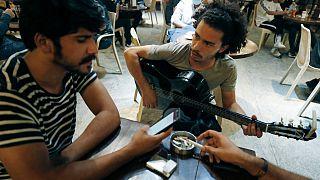عازف الجيتار العراقي محمد، يلعب وهو يجلس مع أصدقائه في مقهى بالعاصمة بغداد، العراق.