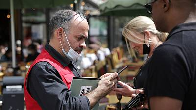 A waiter checks diners' health passes at a restaurant in Paris, 9 August 2021.