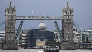 A boat sails down the River Thames in London, Monday Aug. 9, 2021 in front of Tower Bridge that is stuck in the fully open position due to a technical fault.