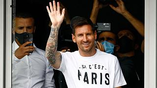 """Lionel Messi, à son arrivée à l'aéroport du Bourget, en région parisienne, portant un t-shirt avec le slogan du PSG """"Ici, c'est Paris"""", le 10 août 2021"""