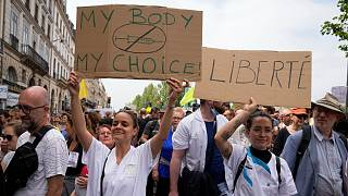Nurses hold placards as they march during an anti-health pass protest in Paris, Saturday, July 17, 2021.